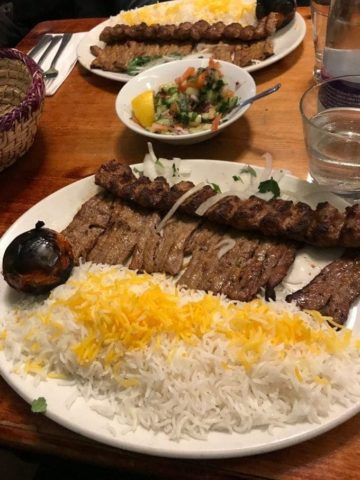 Two plates of rice and kebabs with a side of shirazi salad courses