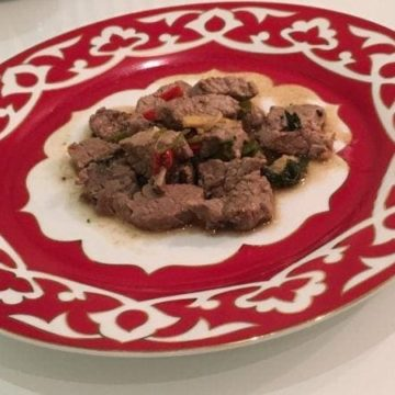 small portion of beef on red and white plate