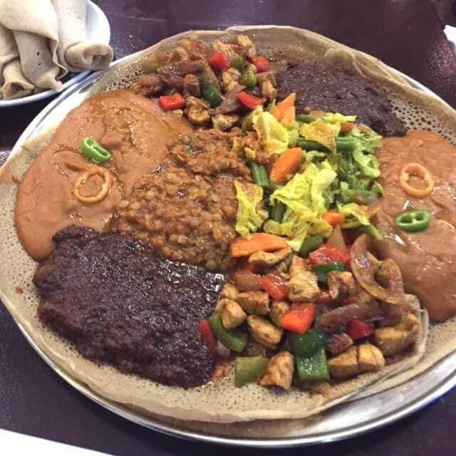 platter of injera with portions of assorted mains