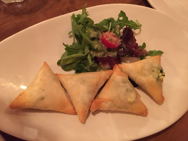 4 triangles of borek with a mini salad on a plate