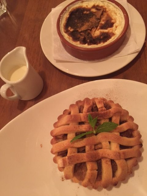 apple tart with a small jug of cream, and rice pudding