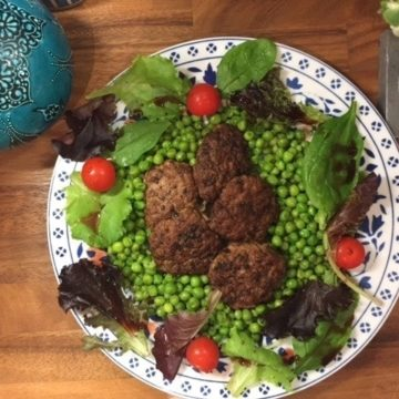 Turkish meatballs on bed of peas on a platter surrounded by salad.