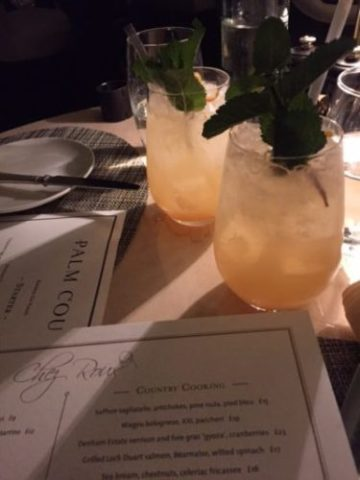 Two yellow drinks on table next to menus
