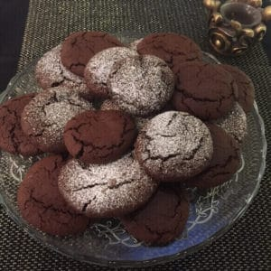 cookies on a plate, some dusted with icing sugar