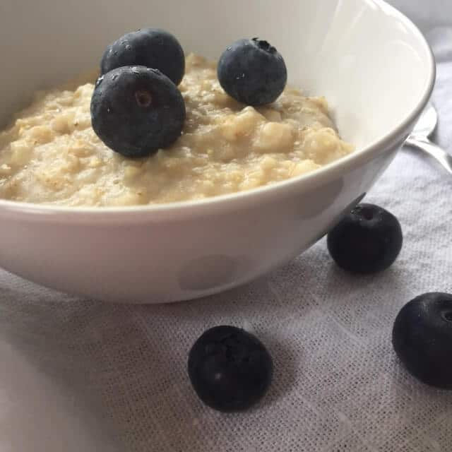 cooked oatmeal with blueberries in small white bowl