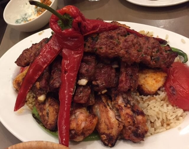 mixed grill meats platter topped with a large red pepper