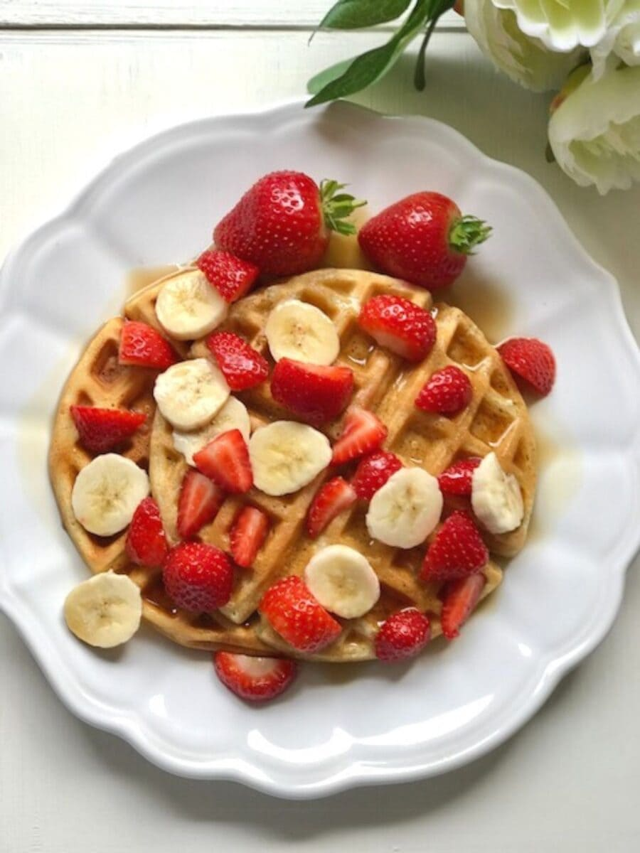 Fluffy waffles covered in sliced banana and strawberries