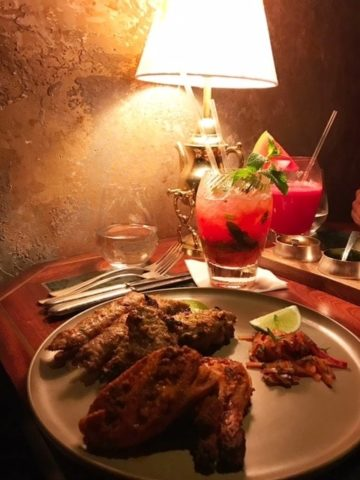 food on plate with red drinks lit by a table lamp