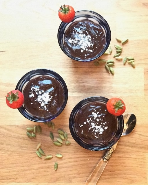 top view of glasses with chocolate pudding and strawberries with scattered cardamom