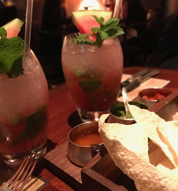 Dining table with poppadums, three dips and watermelon drinks in glasses with crushed ice