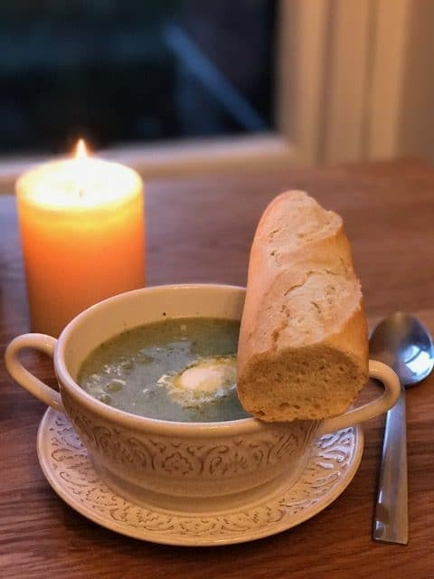 Broccoli soup in white bowl with bread next to a candle