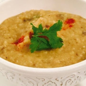 white bowl with yellow dal with coriander leaves and paprika garnish
