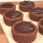 6 cookie cups filled with chocolate on wooden board