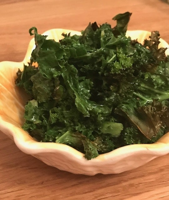 Baked kale in a small yellow bowl