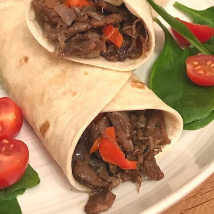 two wraps showing pulled beef filling on plate with salad