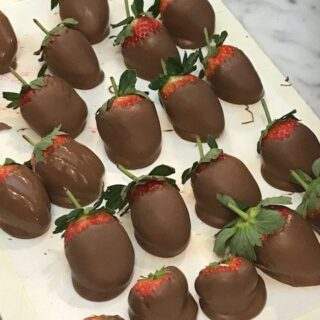 large stawberries dipped in chocolate on parchment paper