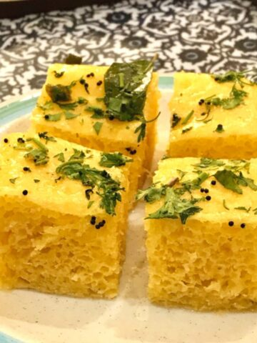 4 small squares of dhokla on a white plate