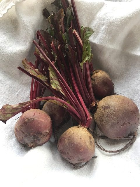 raw beetroot with stems on a white cloth