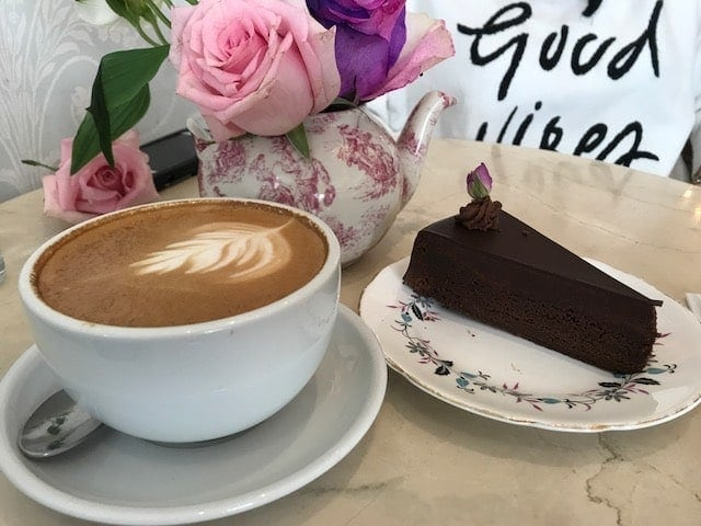 coffee latte and slice of flourless chocolate cake