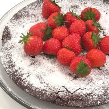 Image of Kladdkaka on glass plate dusted with powdered sugar and whole strawberries.