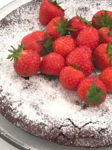 Kladdkaka on glass plate dusted with powdered sugar and whole strawberries