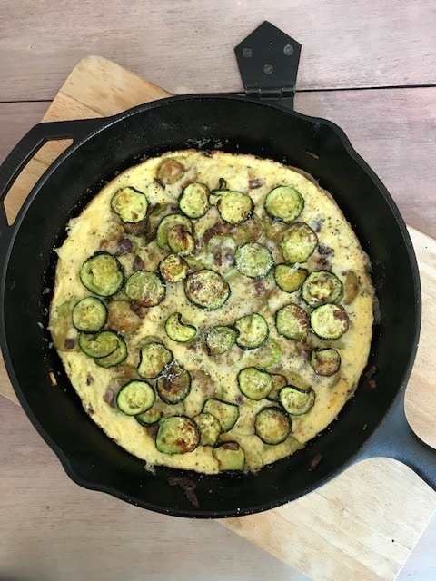 frittata in a skillet on a wodden board