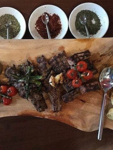 Lamb steak with vegetables on a wooden platter with bowls of dried herbs