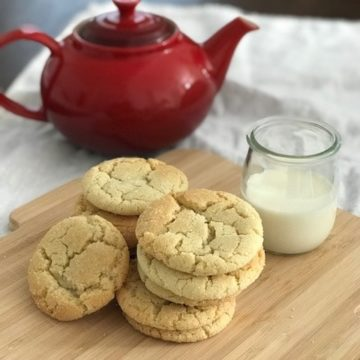 a plie of cookies on a wooden board with a beaker of milk