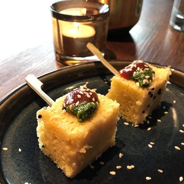 2 rectangles of yellow dhokla with chutney on top