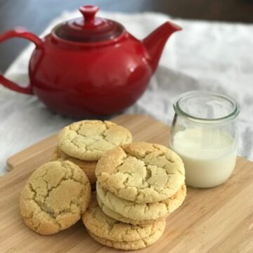 A pile of sugar cookies on a wooden board with a beaker of milk.