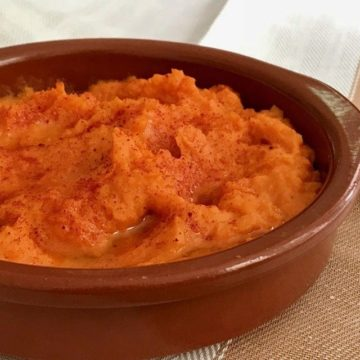 close up of hummus in a shallow terracotta bowl