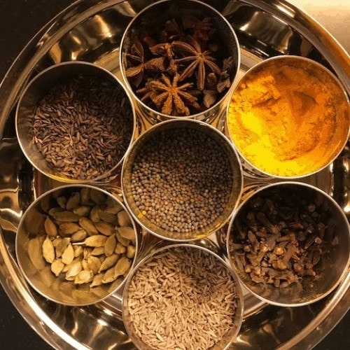 overhead view of a spice box containing small bowls of spices