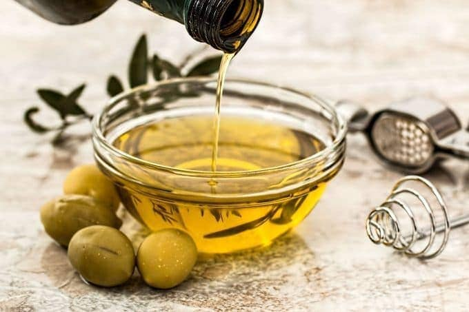 brown bottle pouring olive oil into a bowl next to some olives
