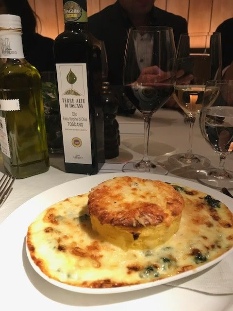 A dish of souffle with cheese and spinach next to a bottle of terre alto oil