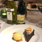 A slice of Sicilian chocolate cake and a scoop of ice cream on a plate with two bottles of olive oil