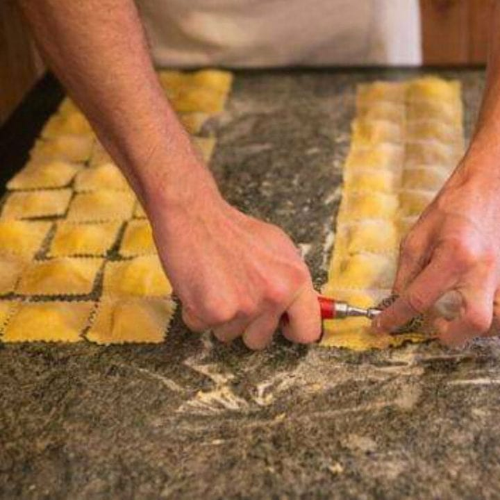 view of hands cutting ravioli