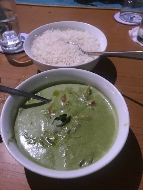 white bowl of thai green curry and another of plain boiled rice