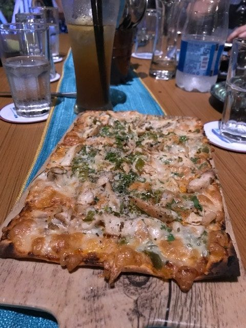 flatbread with pieces of chicken on a wooden board