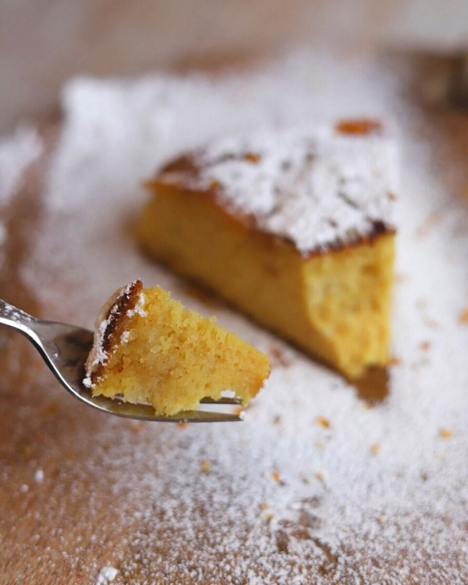 fork with piece of orange cake and slice in the background