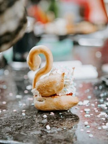 Single undecorated choux pastry swan on counter