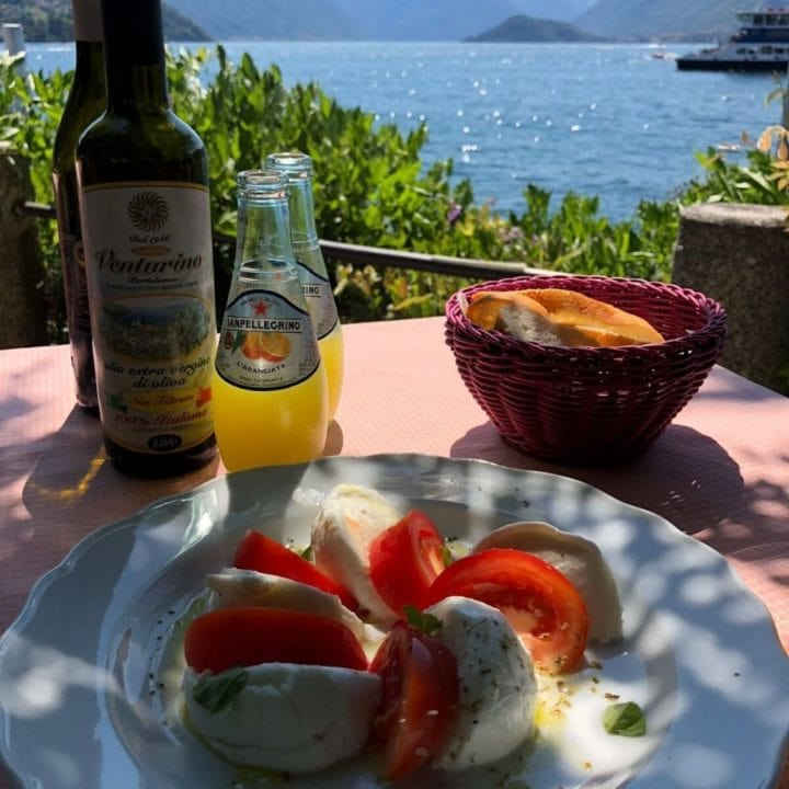 Mozzarella and tomato salad on table with view of the sea
