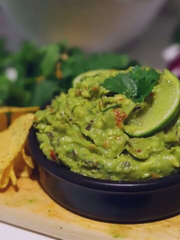 closeup of guacamole in small black bowl