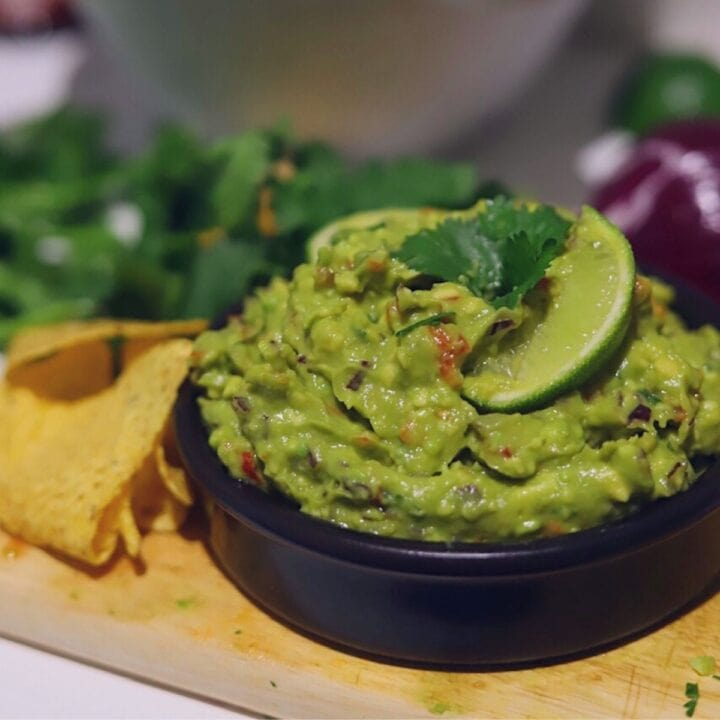 Image of guacamole in small black bowl garnished with cilantro and slice of lime.