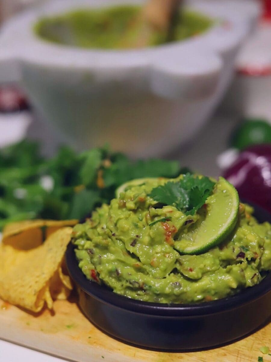Guacamole in a black bowl surrounded by ingredients
