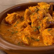 closeup of butter chicken in brown bowl