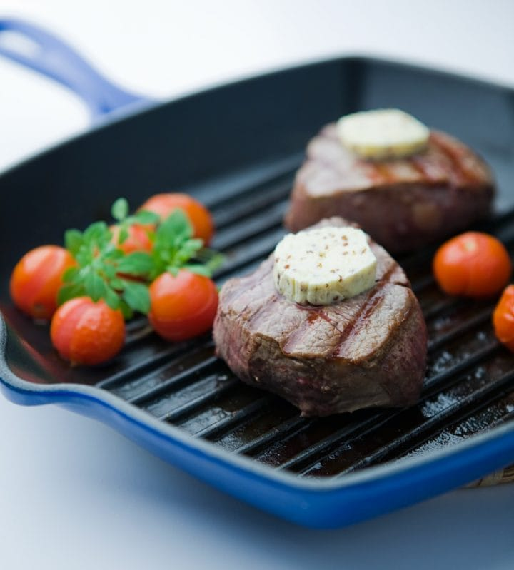 Two steaks in grill pan with rounds of butter on top