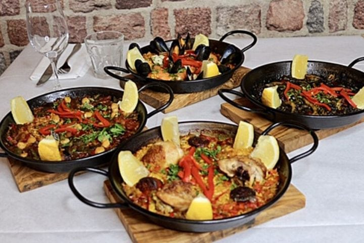 Four paella dishes on table