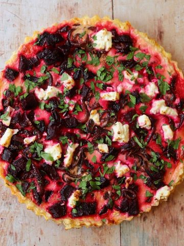 Beet and feta tart on wooden table