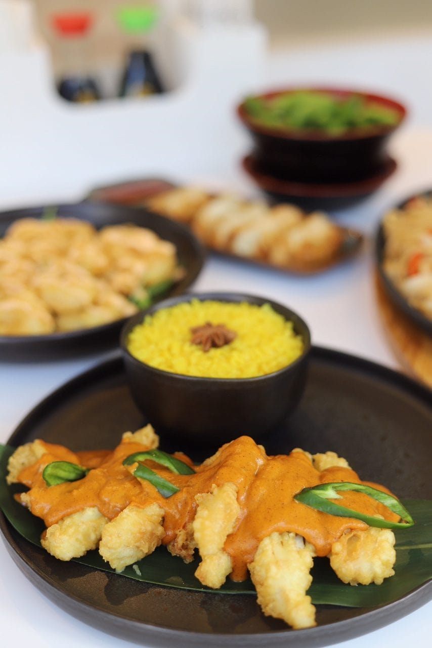 samll dishes of starters and plate of cod curry and rice