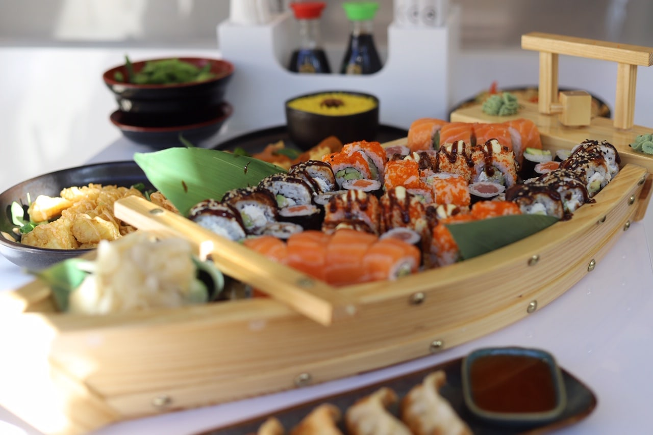 assorted sushi served on small wooden boat on the table